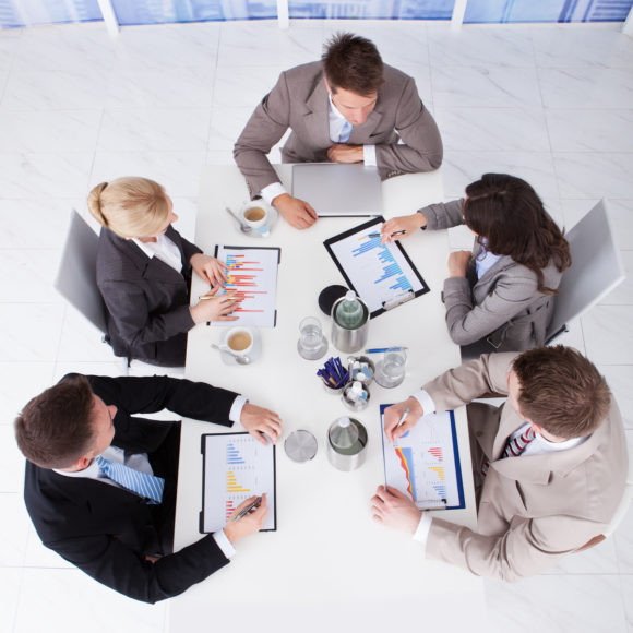 Business People Discussing On Graphs At Conference Table